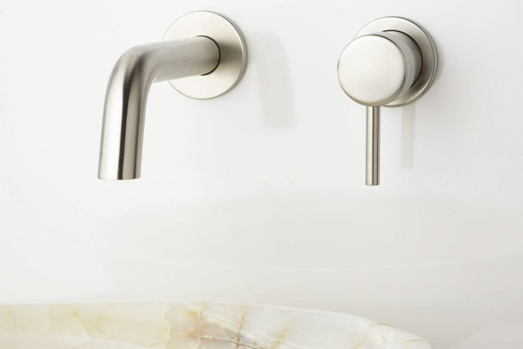 > Close up of modern, shiny, silver-color waterfall faucet
