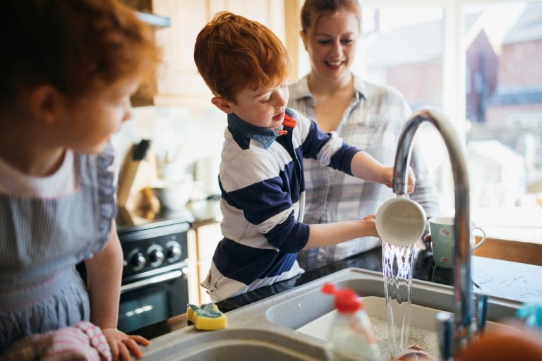 Young boy helping mom manually wash dishes